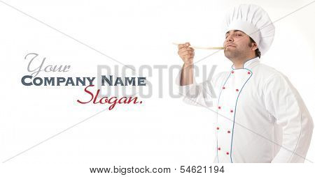 Male cook delightfully smelling the contents of a wooden spoon