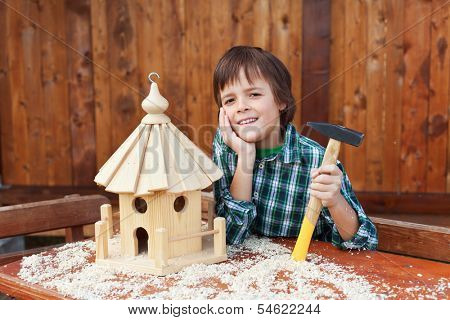 Happy boy building a bird house for placing out bird seeds in winter time