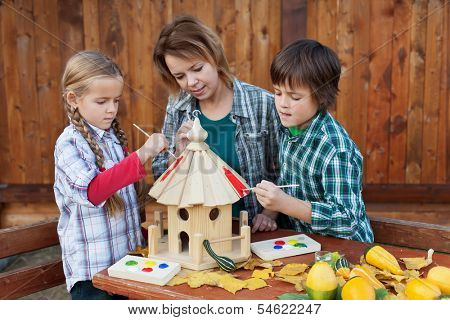 Woman with kids in autumn painting the bird house - preparing it for winter time
