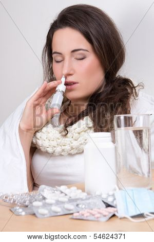 Young Woman Using Nasal Spray In Her Living Room