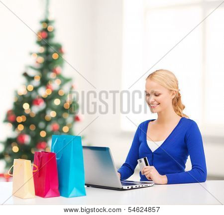 christmas, x-mas and online shopping concept - smiling woman with shopping bags, laptop and credit card