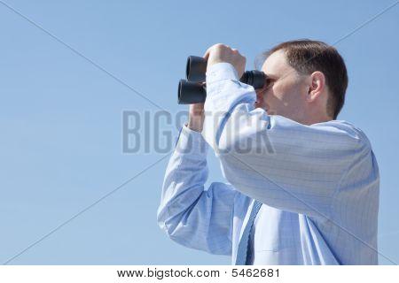 Kaufmann mit einem Fernglas gegen blauen Himmel