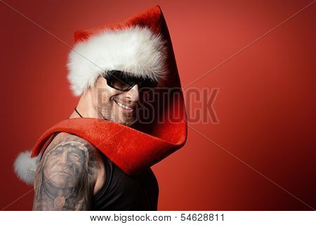 Portrait of a handsome brutal man in Christmas hat. Over red background.