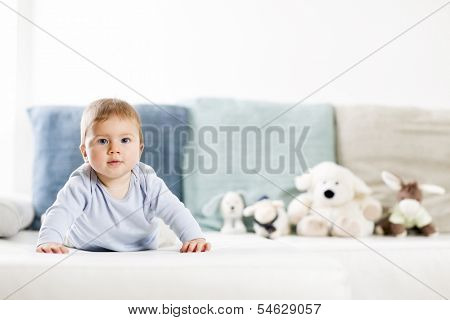 Adorable baby boy with blue eyes in blue shirt lying on belly on sofa and looking straight, blurred toys in background.