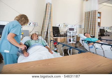 Mature nurse examining patient in post anesthesia care unit