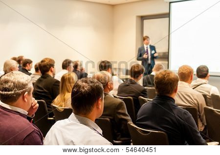 People Sitting At The Business Conference And Speaker At The Screen