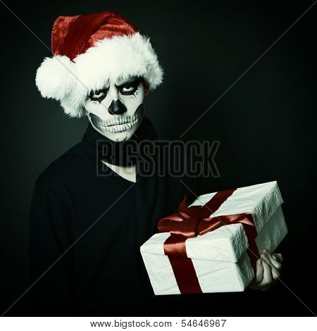 Holiday background of halloween person with terrible skull make-up in santa's hat with gift box over black background