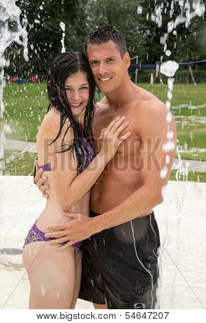 Couple Hugging In A Water Park At Swimming Pool