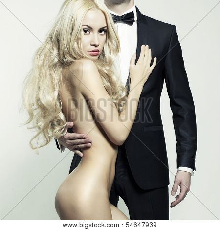 Fashionable photo of beautiful naked lady and man in suit