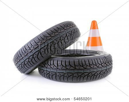 Two winter car tyres and road cone shot on white