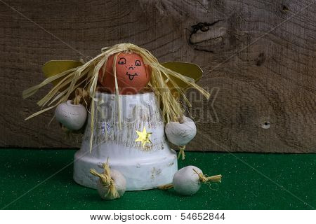 Christmas Angel From Pot On Green Fabric And Rustic Elm Wood