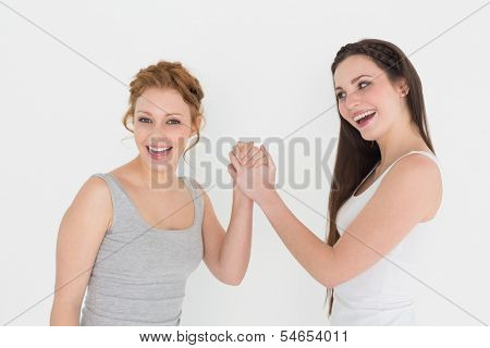 Portrait of two casual young female friends arm wrestling against white background