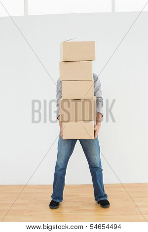 Obscured man carrying boxes in a new house