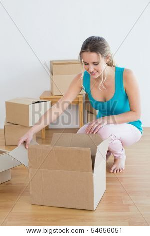 Happy young woman moving in a new house and unwrapping boxes