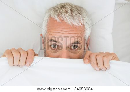 Close-up portrait of a mature shocked man covering face with sheet in bed at home