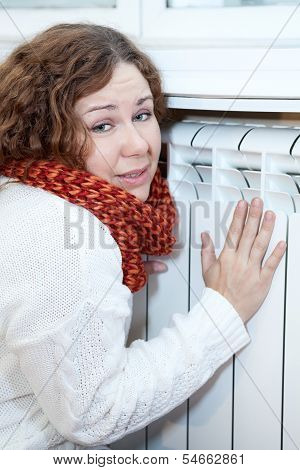 Young Woman Feels Cold Sitting Near Central Heating Convector