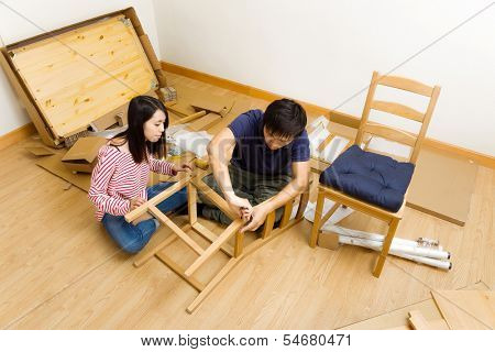 Asian couple assembling furniture for new house