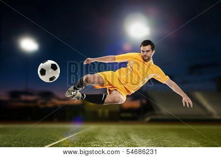 Soccer Player kicking the ball ina football stadium at night