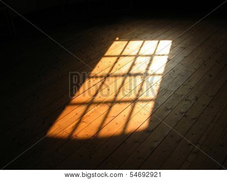 Sunlight from window falling on wooden floor in darkened room.