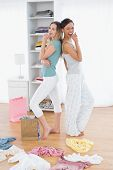 Side view of two smiling young women pretending to sing with shopping bags and clothes on floor at h