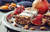 stock photo of pomegranate  - Granola bars on plate with nuts pomegranate and dried fruits on wooden background - JPG