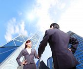 stock photo of handshake  - Business woman and man handshake with business office building background asian hong kong - JPG