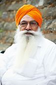 stock photo of rajasthani  - Portrait of elderly Indian sikh man in turban with bushy beard - JPG