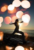 foto of virabhadrasana  - warrior II yoga pose on beach with sunrise and flares - JPG
