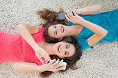 image of slumber party  - High angle view of two young female friends lying on rug and text messaging in the living room at home - JPG