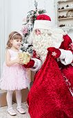 foto of saint-nicolas  - Saint Nicolas gives Christmas gifts to the little girl - JPG