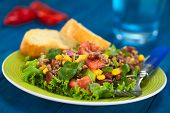 stock photo of sweet-corn  - Chili con carne salad made of mincemeat kidney beans watercress green bell pepper tomato sweet corn and red onions served on lettuce on a plate with fork and baguette slices