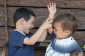 stock photo of misbehaving  - Two children boys toddler and his older brother play fighting concept of sibling rivalry - JPG