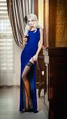 Young beautiful luxurious woman in long elegant blue dress holding a glass of wine