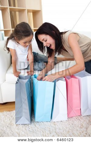 Happy Mother And Daughter Unpacking Shopping Bags