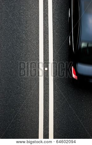 Double White Lines Divider On Blacktop With A Car Passing