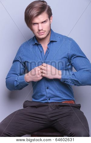 young sexy man unbuttoning his shirt for the camera in studio