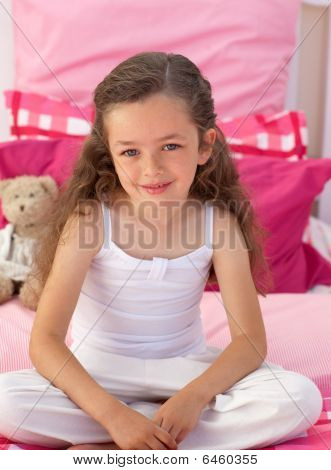 Little Girl Sitting On Bed