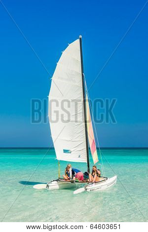 VARADERO,CUBA - APRIL 26,2014: Beautiful girls sailing on a colorful catamaran on a sunny day at the beach