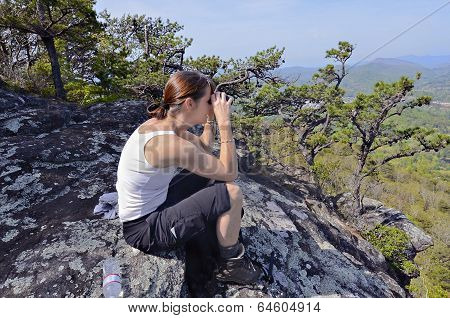 Woman With Binoculars On A Mountain