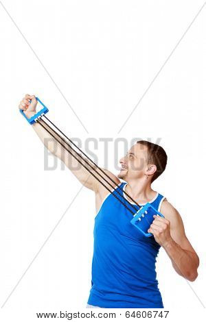 Smiling sportsman doing fitness exercises with expander over white background