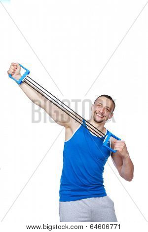 Cheerful sportsman doing fitness exercises with expander over white background