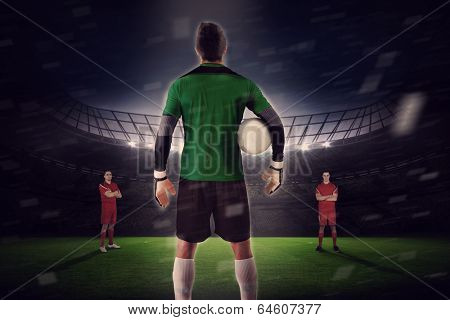 Composite image of goalie facing opposition against large football stadium with fans in yellow