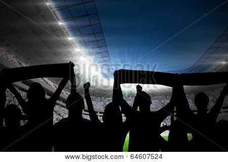 Silhouettes of football supporters against football stadium