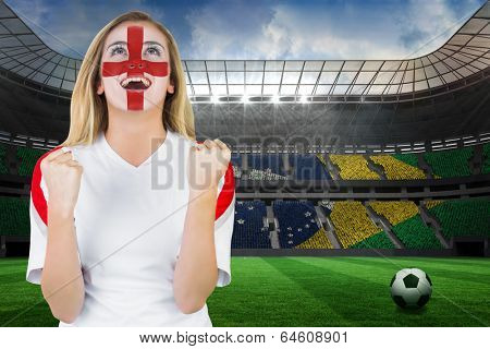 Excited fan england in face paint cheering against large football stadium with brasilian fans