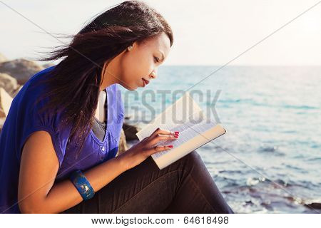 Young Girl Studying Her Bible By The Sea