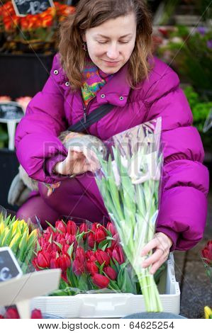Beautiful Young Woman Selecting Flowers At Market