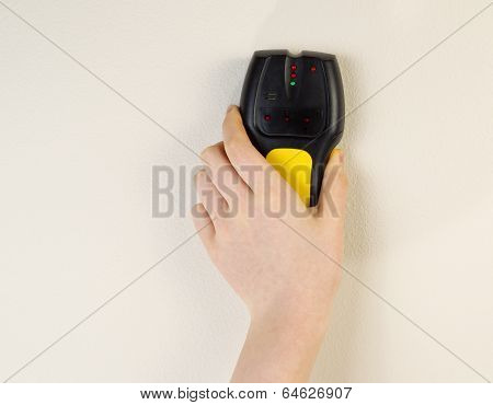 Electronic Stud Finder Against Interior Wall Of Home