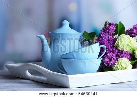 Composition with tea set and bouquet of beautiful spring flowers on tray, on wooden table, on bright background