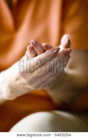 Close-up of elderly woman rubbing her hands