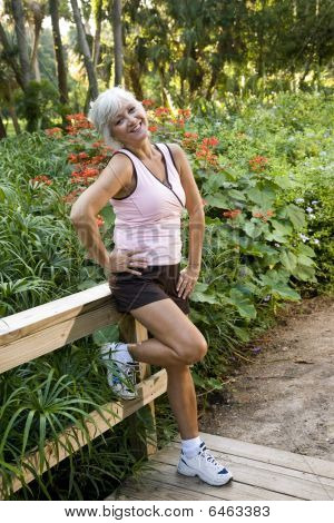 Woman in workout clothes standing on park bridge